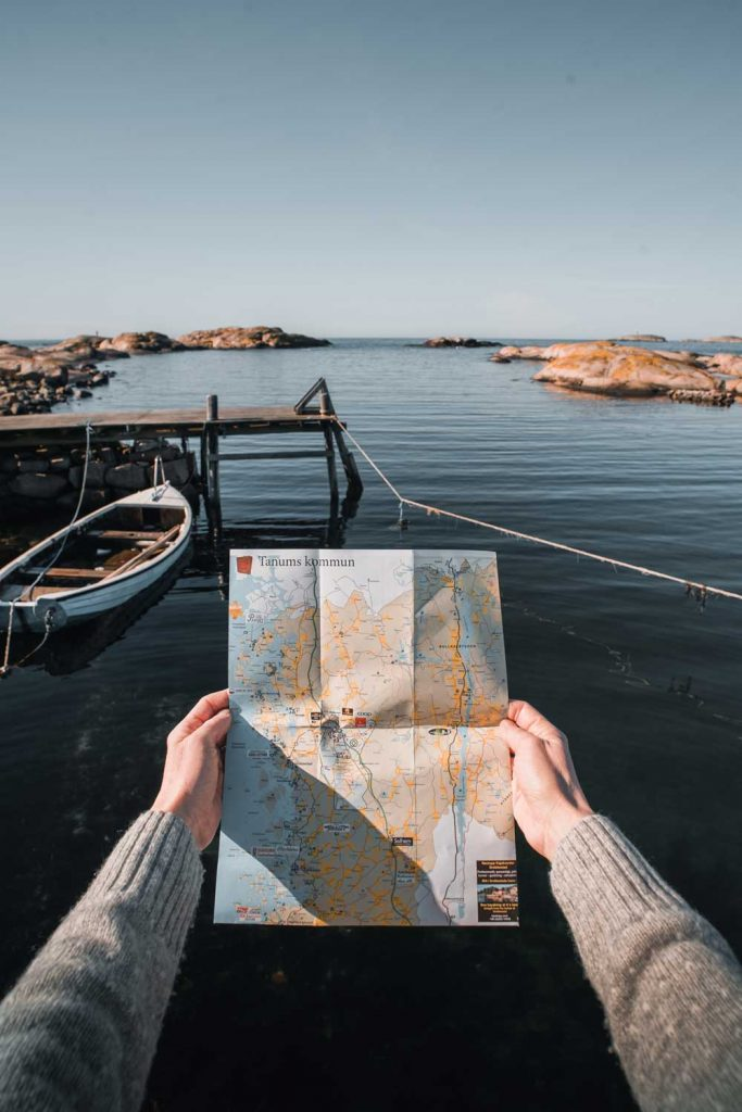 Person håller upp en karta under sin vandring längs havet på västkusten i sverige