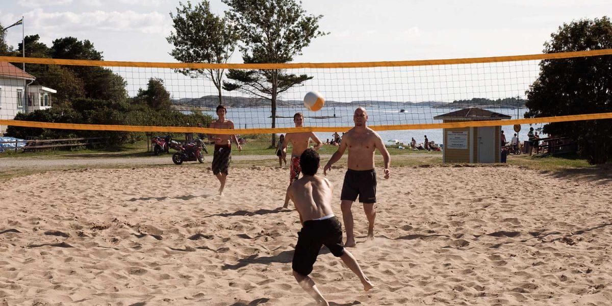 Kompisar spelar volleyboll på stranden i sanden vid havet på TanumStrand på Västkusten