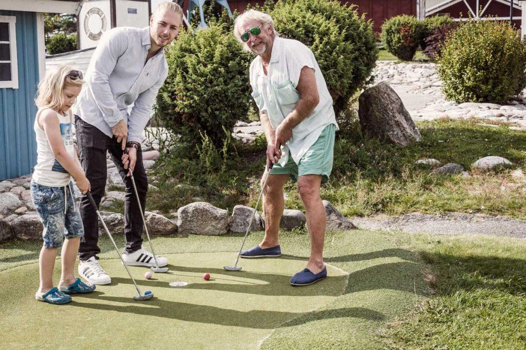 En familj med barn och vuxna spelar minigolf i på TanumStrand Grebbestad