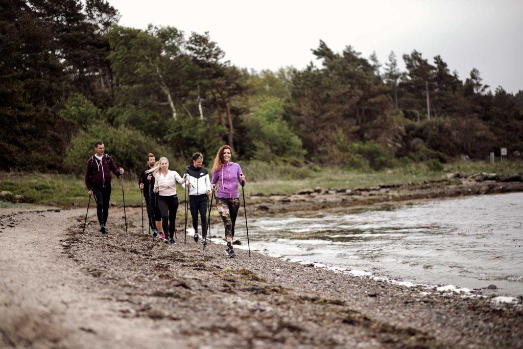 Vänner vandrar längs strandkanten vid havet i Bohuslän mellan Grebbestad och Fjällbacka