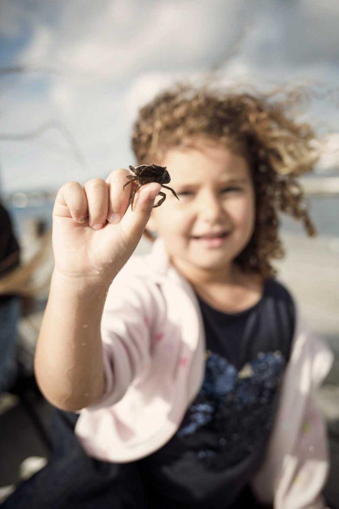Tjej håller upp en krabba hon precis fångat på stranden vid TanumStrand