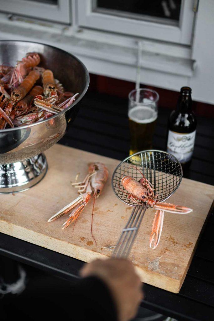Man kokar nyfångade havskräftor i sjöboden på bryggan vid havet i norra Bohuslän