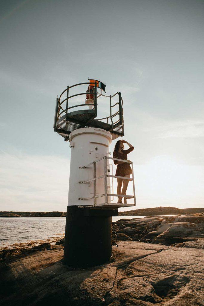 Kvinna som står och kikar ut från en fyr på klipporna vid havet på den svenska västkusten