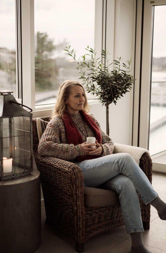 Kvinna dricker te och myser vid havet på vintern i Bohuslän