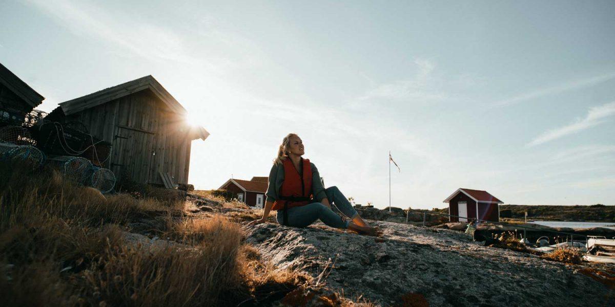 Kvinna med flytväst som njuter av havsutsikten vid havet