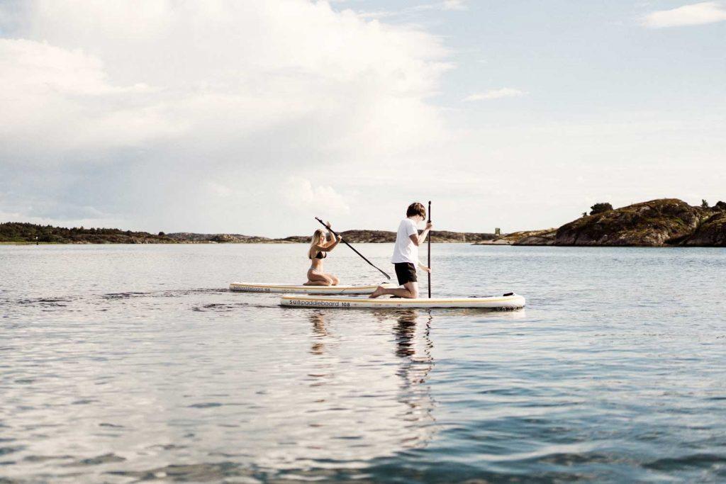 Två vänner paddlar stand up paddle board på havet i Bohuslän nära Grebbestad