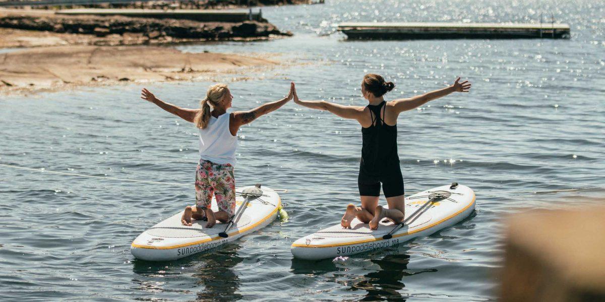 Kvinnor paddlar stand up paddle board I Bohuslän