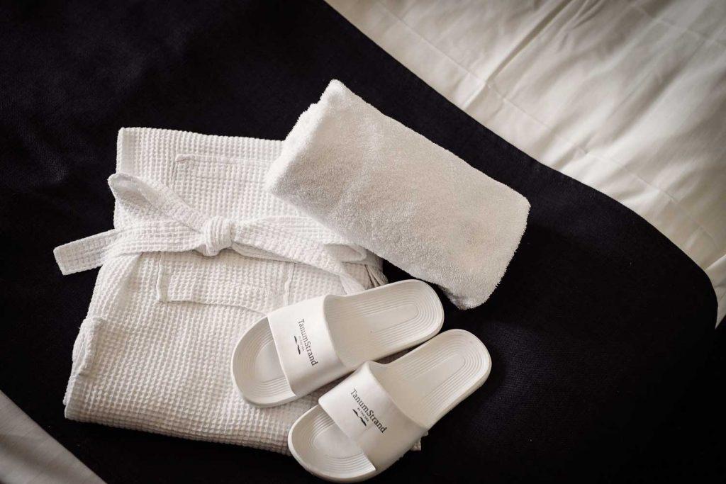 Badrock, handduk och tofflor på hotellrummet på spahotellet Tanumstrand vid havet