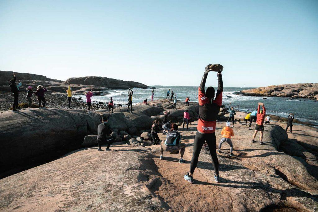 En stor grupp tränar styrkträning utomhus på klipporna vid havet på TanumStrand