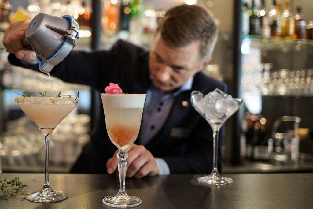 Bartender blandar cocktails i lobbybaren på TanumStrand