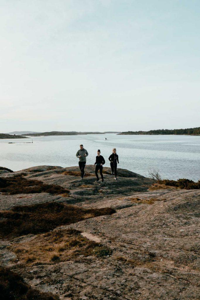 Kompisar som är ute på en löprunda i bergen längs klipporna på kusten