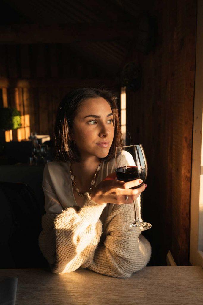 Kvinna som dricker rödvin i glas i sjöboden vid havet