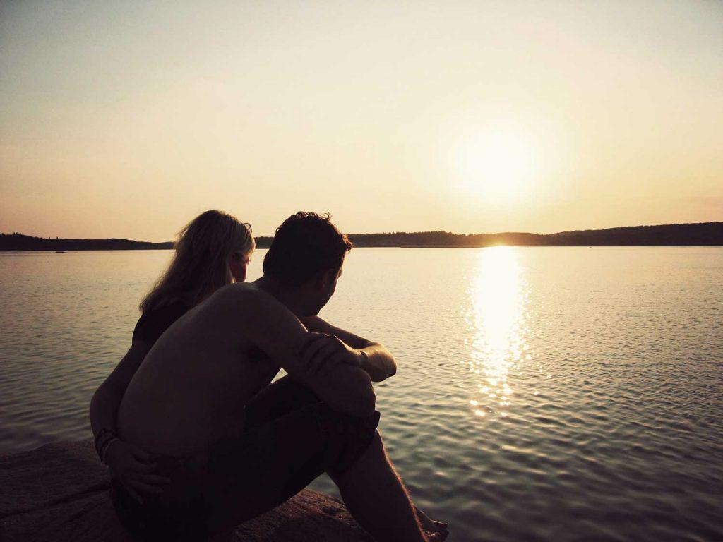 Par som myser i solnedgången på klipporna på hotell på Västkusten