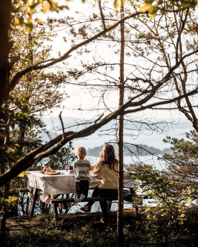 Mor och son fikar på en bänk i skogen med utsikt över havet och naturen