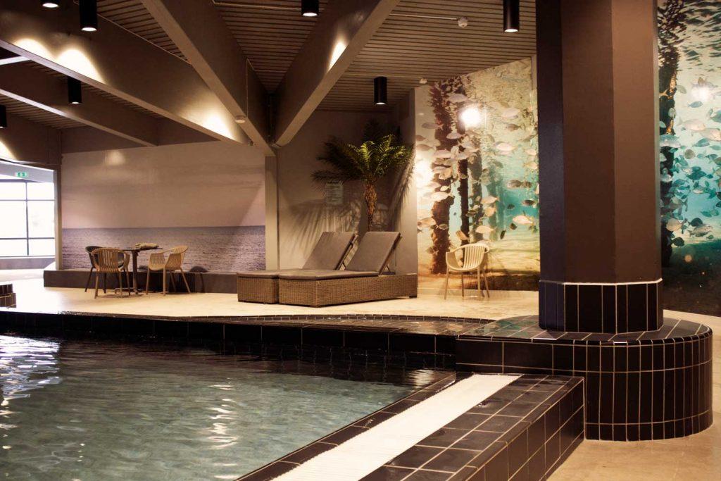 Bild på pool och relaxstolar inne på äventyrsbadet för barnfamiljer på TanumStrand