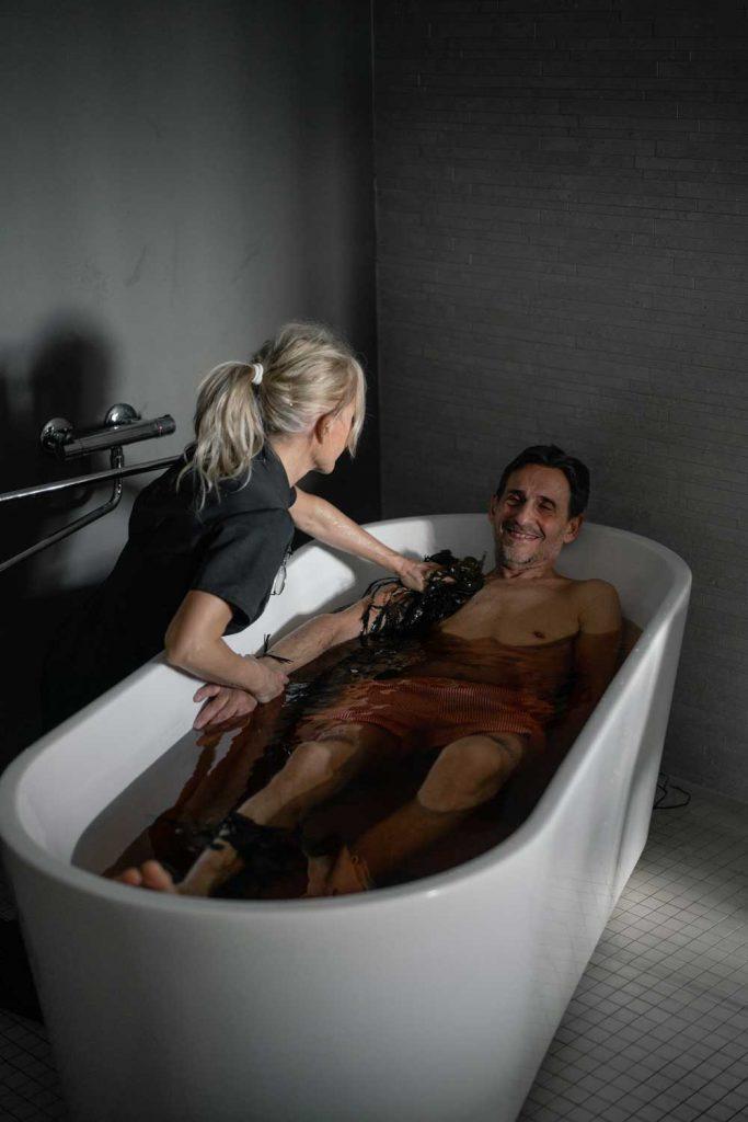 Man testar behandling med tångskrubb och massage i ett badkar på spa vid havet