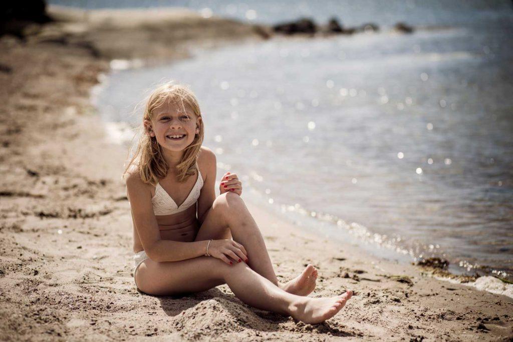 En flicka badar tillsammans med sin familj på stranden vid havet på västkusten