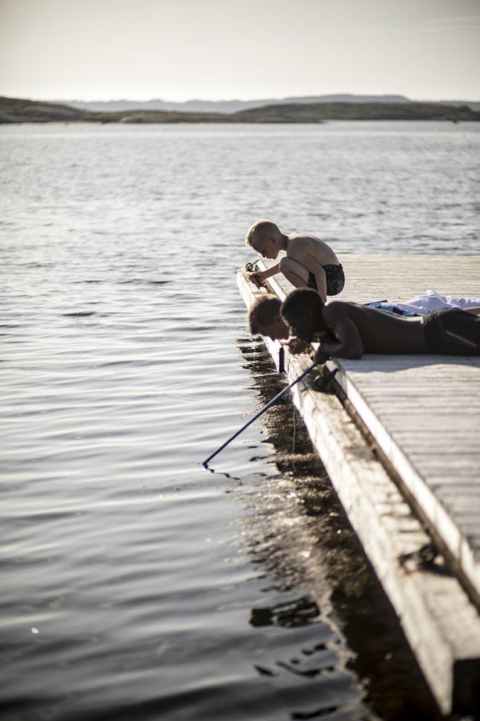 Barn fiskar krabbor i havet under sommaren på TanumStrand