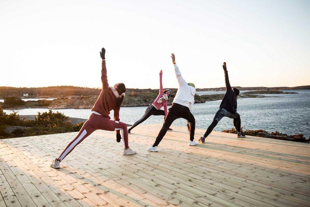 Deltagare på en träningsweekend tränar utomhus vid havet med vacker havsutsikt i skärgården på Västkusten i Sverige