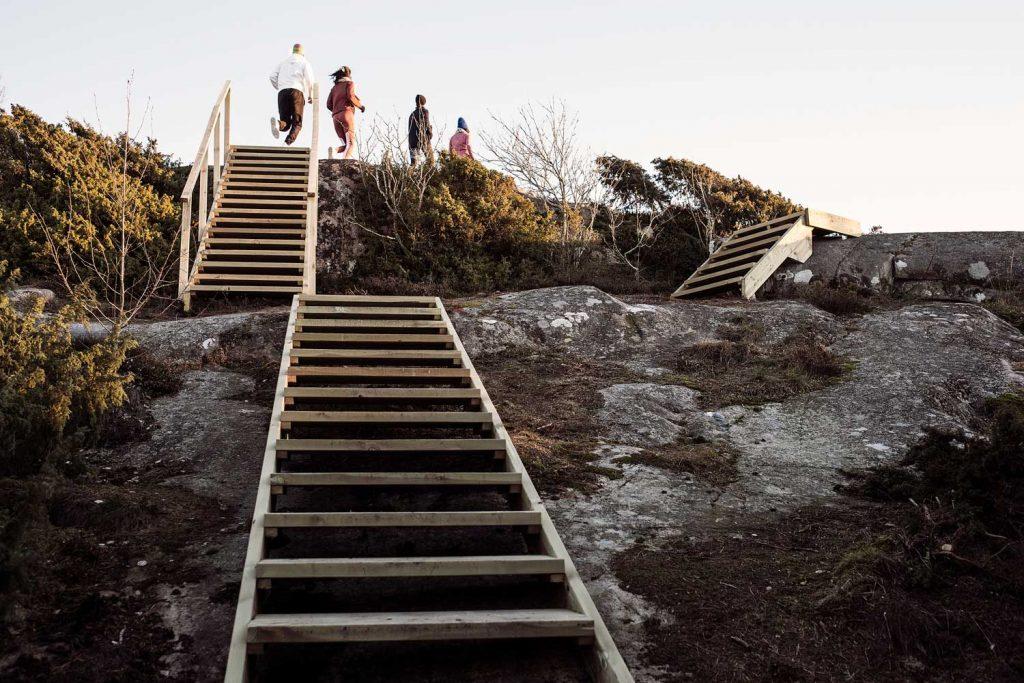 Deltagare på en träningsresa löper längs klipporna vid havet på västkusten i sverige