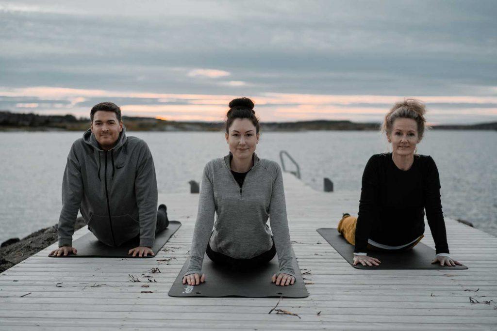 Tre personer utövar yoga utomhus på bryggan under en träningsresa i Sverige