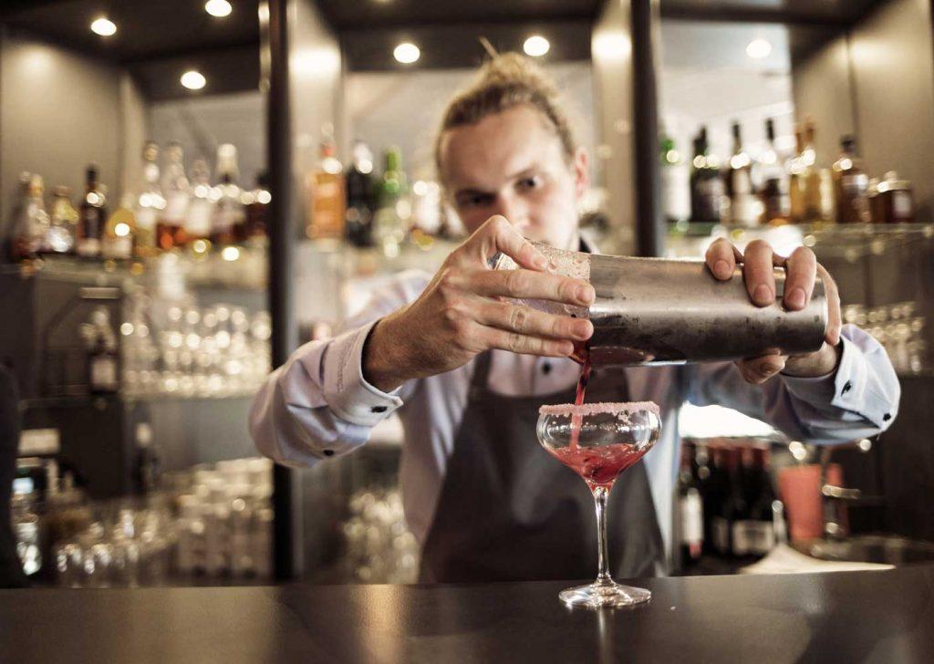En bartender serverar goda cocktails till gäster i baren på hotell vid havet