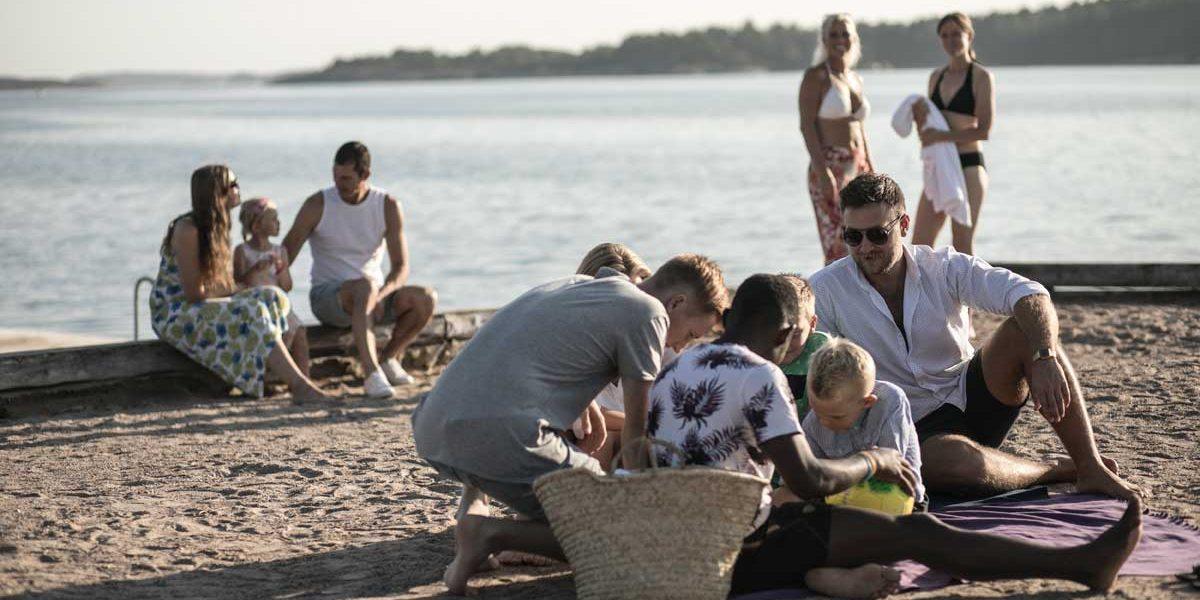 Familj med barn leker utomhus på stranden vid havet i Bohuslän på Västkusten i Sverige