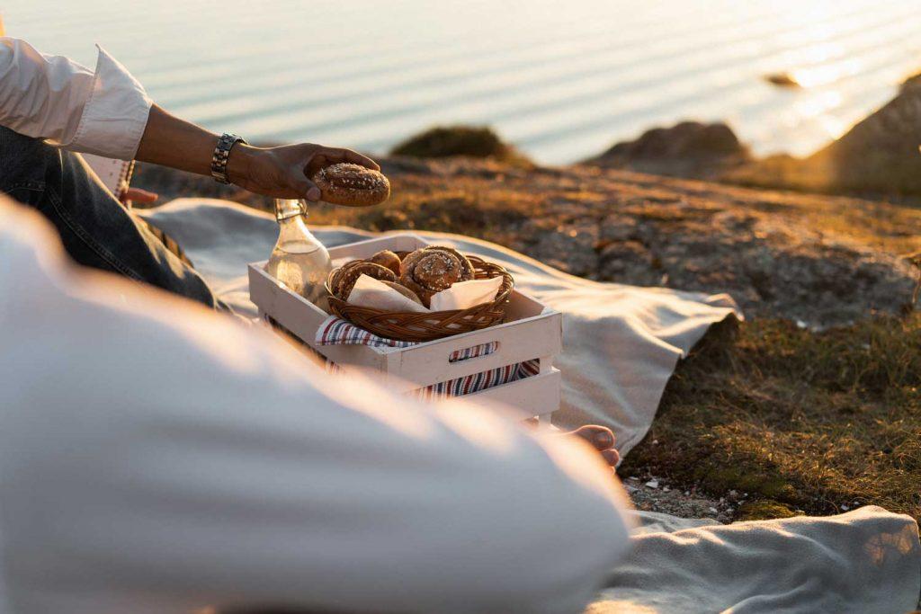Gäster njuter av picknick med nybakat kanelbullar och kall mjölk på klipporna vid stranden på Västkusten