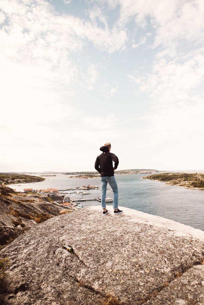 Man står på en klippa med vacker havsutsikt över Grebbestads skärgård i Norra Bohuslän i Västsverige