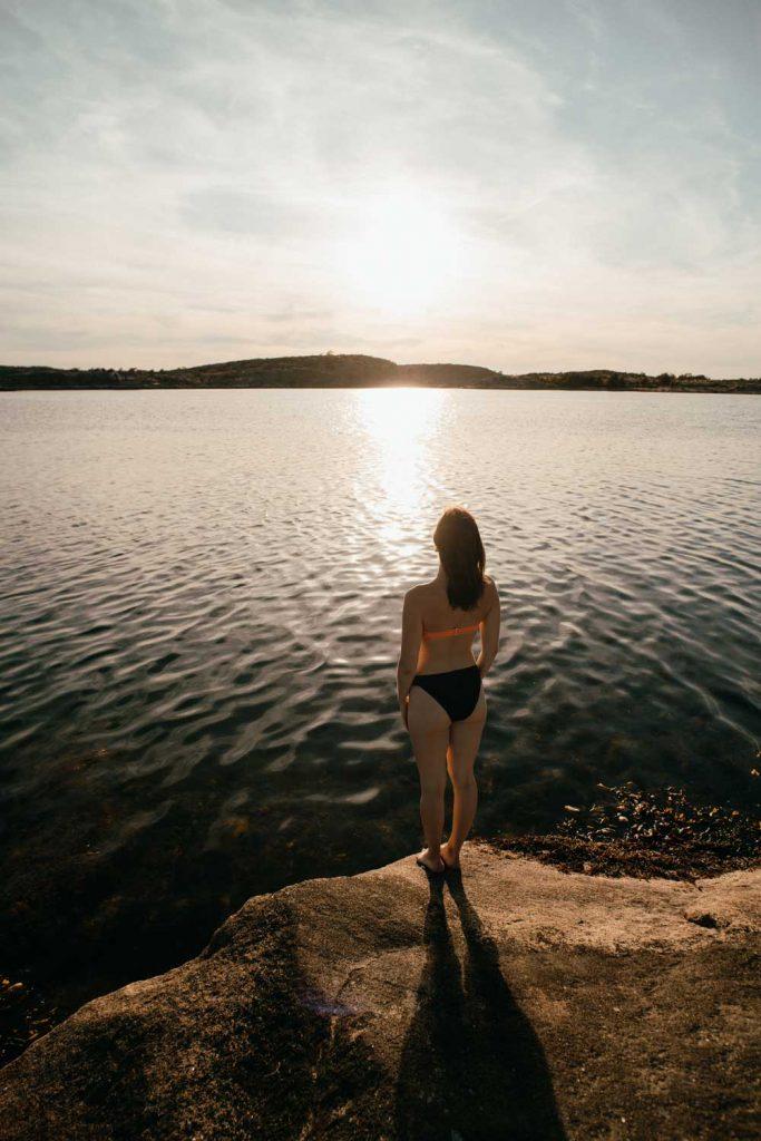 Kvinna tar ett dopp i havet vid klipporna i Bohuslän på Västkusten i Sverige