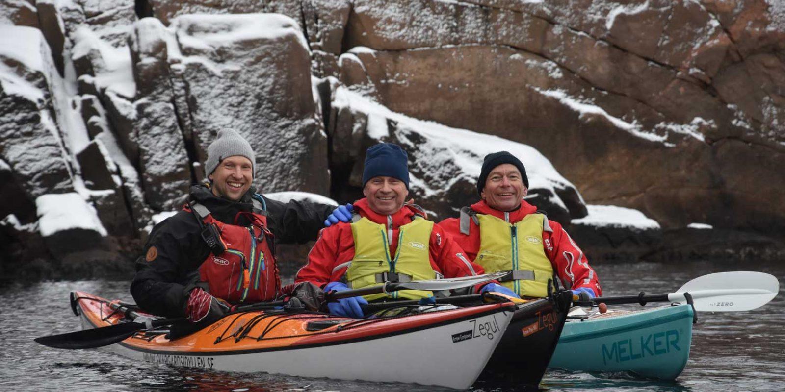 Personer paddlar kajak på vintern i norra Bohuslän tillsammans med en professionell guide från Skärgårdsidyllen