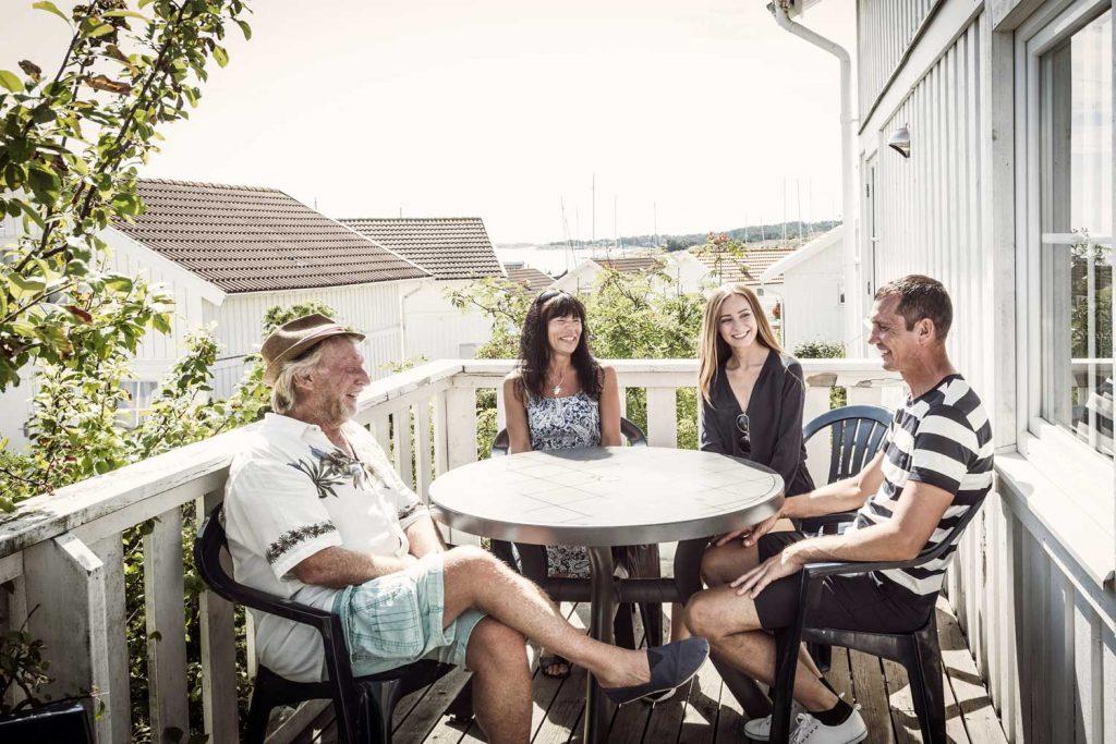 Familj fikar på verandan till deras stuga som de hyrt vid havet på Västkusten i Sverige