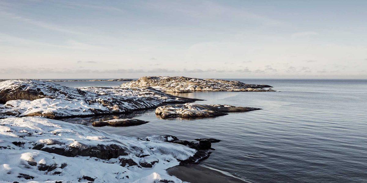 Vacker vinterbild på snötäckta klippor vid havet i Norra Bohuslän i Västsverige